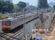 Commuter line melintas diantara tiang pancang pembangunan jalur kereta Bandara di Jakarta, Ahad (27\11).