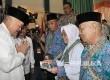 Gubernur Alex Noerdin menyerahkan bantuan uang transportasi selama berada di tanah suci yang diserahkan secara simbolis kepada perwakilan calhaj dan memasangkan jaket kepada petugas haji yang mendampingi calhaj dalam kloter pertama embarkasi Palembang.
