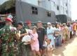 Anggota Kopassus membagikan paket sembako untuk korban banjir di rumah susun Penjaringan Muara Baru ,Jakarta Utara,Kamis (7/2).  (dok. Penerangan Kopassus)