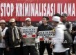 Masa Hizbut Tahrir Indonesia (HTI) melakukan aksi Menolak Kriminalisasi dan Pelecehan Terhadap Ulama saat berlangsungnya Hari Bebas Kendaraan Bermotor (HBKB) di kawasan silang Monas, Jakarta, Ahad (5/2).