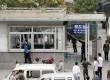 Pekerja membersihkan pecahan kaca dari jendela ruang keamanan yang pecah di pintu masuk pabrik Foxconn Tech-Industri Park di Taiyuan, provinsi Shanxi, Senin (24/9). (Reuters)