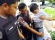 Petugas kepolisian menggeledah pakaian pelajar yang terjaring dalam razia di kawasan jalan Kuningan, Jakarta Selatan, Selasa (3/4).