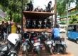 Petugas merapikan kendaraan bermotor di atas truk untuk paket motor gratis di Jakarta, Ahad (18/6).