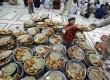 Seorang anak Pakistan membagikan piring makanan kepada jamaah yang hendak berbuka puasa di sebuah masjid di Karachi, Pakistan, Sabtu (21/7).  (Shakil Adil/AP)