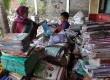 Seorang Guru SDN 07 Petamburan menyortir buku-buku yang basah akibat banjir yang merendam kawasan Petamburan Jakarta Barat,Senin (21/1).(Republika/Rakhmawaty La'lang)
