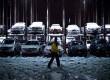 Seorang petugas parkir berjalan melewati mobil yang tertutup salju setelah diterpa badai Nor'easter di New York, Rabu (8/11). (Reuters/Andrew Burton)