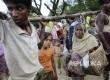 Pria Rohingya membawa ibu mereka yang sakit saat mereka tiba di perbatasan Bangladesh di Teknaf, Bangladesh, Sabtu (9/9).