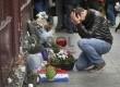 Seorang pria termenung seusai meletakkan karangan bunga di luar restoran Le Carillon, Paris, Sabtu (14/11). REUTERS / Christian Hartman