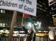 Seorang wanita membawa bendera Palestina saat melakukan aksi protes di seberang kantor konsulat Israel di New York, Jumat (16/11). (Reuters/Carlo Allegri)