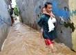 Seorang warga sambil menggendong anaknya melintasi banjir di Jalan Kampung Melayu Kecil, Kelurahan Bukit Duri, Kecamatan Tebet, Jakarta, Selasa ( 5/3).  (Republika/Prayogi)