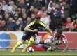 Striker Arsenal Olivier Giroud jatuh bangun berebut bola dengan pemain Stoke City Glen Johnson dalam pertandingan Liga Inggris, Sabtu (13/5).