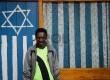 Warga berfoto di depan rumah dengan logo Israel atau Bintang Daud di Tolikara, Papua, Jumat (24/7).  (Republika/Raisan Al Farisi)