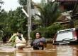 Warga melintasi banjir di Perumahan Bumi Nasio Indah, Jatiasih, Bekasi, Jawa Barat, Kamis (18/4).  (Republika/Adhi Wicaksono)