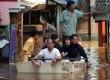 Warga memanfaatkan perahu kecil untuk melintasi genangan air banjir di Kawasan Jatinegara,Jakarta Timur, Rabu (13/2).  (Republika/Prayogi)