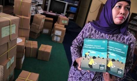 Seorang guru menunjukkan buku paket kurikulum 2013 mata pelajaran pendidikan jasmani olahraga dan kesehatan di SMPN 11 Tegal, Jateng, Selasa (9/9).