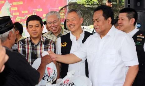 Menteri Perdagangan Rachmat Gobel, Menteri PAN dan RB Yuddy Chrisnandi dan pendiri Artha Graha Tomy Winata membagikan sembako saat pembukaan pasar murah di Jakarta,Ahad (30/11). (foto : mgROL29)