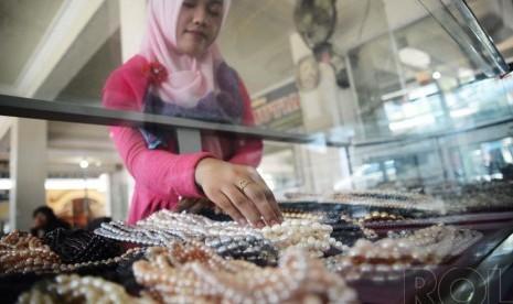 Penjual menunjukkan perhiasan berupa mutiara air tawar yang dijual di sentra pusat perhiasan mutiara di Kawasan Sekarbela, Mataram, Nusa Tenggara Barat, Ahad (21/12).( Republika/Raisan Al Farisi)