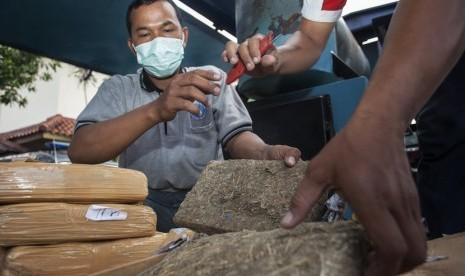Petugas Badan Narkotika Nasional (BNN) bersiap memusnahkan barang bukti ganja dan sabu-sabu yang berhasil disita di Kantor BNN, Jakarta Timur, Jumat (16/1).   (Antara/Sigid Kurniawan)