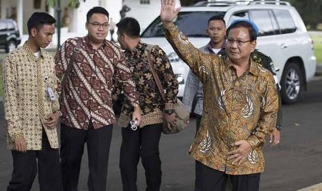 Ketua Dewan Pembina Partai Gerindra Prabowo Subianto (kanan) melambaikan tangan ketika berjalan menuju ruang tunggu setibanya di Istana Kepresidenan Bogor, Jawa Barat, Kamis (29/1).  (Antara/Widodo S. Jusuf)