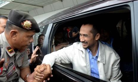 Ketua  KPK non aktif , Abraham Samad (kanan) bersalaman dengan polisi saat tiba di Bandar Udara Internasional Sultan Hasanuddin, Makassar, Sulawesi Selatan, Selasa (24/2).  (Antara/Sahrul Manda Tikupadang)