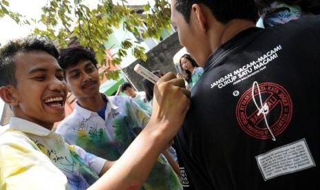Puluhan siswa SMK melakukan aksi mencoret baju seragam seusai melaksanakan Ujian Nasional (UN) di daerah Pancoran Mas, Depok, Jawa Barat, Rabu (16/4).  (foto: MgROL_34)