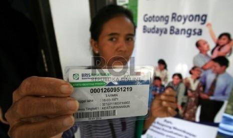 Seorang warga menunjukan kartu BPJS Kesehatan.