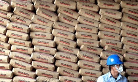 A man stands with a stack of cement sacks produced by PT Semen Gresik in Tuba, East Java. (illustration)