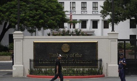 A man walks past the U.S. Embassy in Manila, Philippines on Thursday Sept. 13, 2012 as its flag is on half mast following the death of U.S. diplomats in Libya. Manila police tightened security in the area following the attack that killed the U.S. ambassado