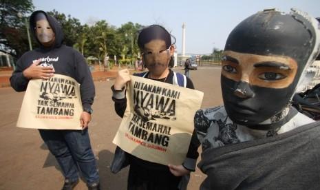 Aktivis melakukan teatrikal saat menggelar Aksi Solidaritas untuk Salim Kancil dan Tosan di depan Istana Negara, Jakarta, Kamis (1/10).