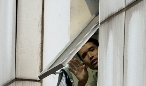 An imigrant from Afghanistan waves his hand from a window in a shelter in Tanjung Priok Jakarta, recently. (illustration)