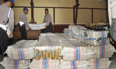 Anggota polisi menggotong karung berisi ganja bagian dari 1,7 ton ganja kering yang disita dari bandar narkoba di Serang, Banten, Rabu (2/12).