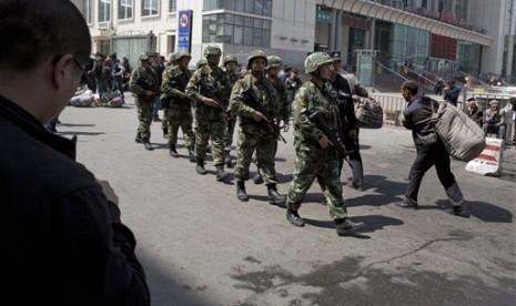 Angkatan bersenjata Cina saat memeriksa area bekas ledakan bom di stasiun kereta api Urumqi, Xinjiang.