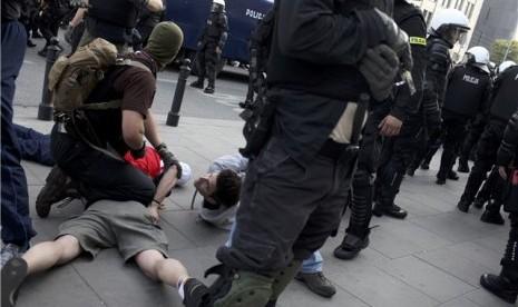 Aparat kepolisian anti-huru hara Polandia menahan suporter yang terlibat perkelahian di Piala Eropa 2012 Polandia-Ukraina.