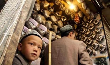 Bocah Uighur saat membantu ayahnya berjualan kopiah di Kota Urumqi, Xinjiang.