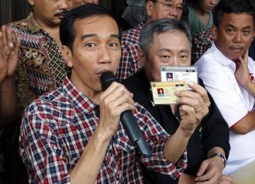 Calon Gubernur Joko Widodo memperlihatkan kartu sehat dan kartu pendidikan, di Jalan Gajah Mada-Hayam Wuruk, Ahad (1/3). (Republika/Adhi Wicaksono)