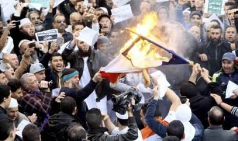 Demonstran di Aljazair membakar bendera Prancis usai shalat Jumat (17/1). Aksi tersebut merupakan bentuk protes terhadap Charlie Hebdo yang menerbitkan edisi terbaru dengan kartun Nabi Muhammad.