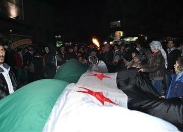 Demonstran menggelar long march dengan membawa bendera Suriah dalam aksi demontrasinya menentang rezim Presiden Bashar Assad di Kedssaya, Damascus, Suriah, Sabtu (4/2) malam.