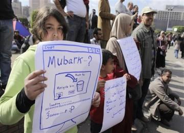 Demonstran cilikdi Kairo, Senin (31/1), memegang poster yang menyerukan Presiden Mubarak mundur.