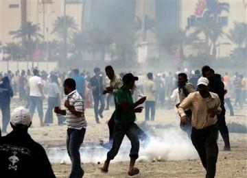 Demonstran melarikan diri dari gas air mata yang ditembakkan polisi di Manama, Ahad (13/3).