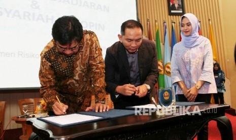 Direktur Kepatuhan dan Manajemen Resiko Bank Syariah Bukopin (BSB) Adil Syahputra (kiri) menandatangani perjanjian kerjasama dengan Direktur Kerja Sama dan Korporasi Akademik Universitas Padjadjaran (Unpad) Dwi Purnomo tentang penggunaan jasa layanan dan p