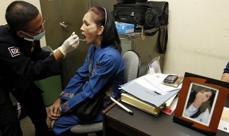 Disaster Victim Identification (DVI) personnel from Indonesian police (left) takes DNA sample from a relative of one of Sukhoi victims at Halim Perdanakusuma Airport, Jakarta, Thursday.