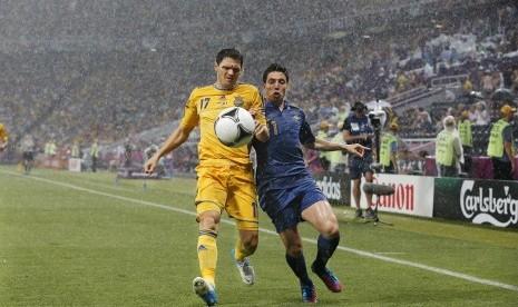 Duel antara Samir Nasri dan pemain Ukraina Taras Mikhalik di tengah hujan deras yang mengguyur stadion Donbass Arena