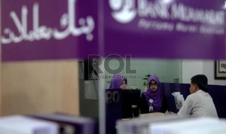 Ekonomi Syariah Solusi Krisis Global: Karyawan melayani nasabah berada di kantor Bank Muamalat, Jakarta, Kamis (9/4).