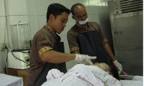 "Fakhru Agnia (left) applies some cosmetics to his ""client""."