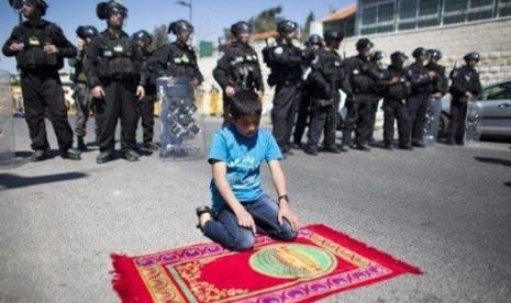 Foto seorang bocah laki-laki yang sedang shalat membelakangi barisan tentara Israel