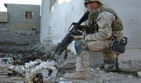 Foto seorang tentara Amerika Serikat sedang mengacungkan senjata ke jenazah pejuang Irak.