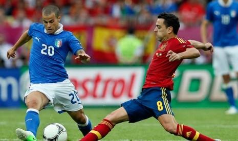 Gelandang Spanyol, Xavi Hernandez dan pemain Italia Sebastian Giovinco berebut bola pada laga pembuka Grup C di Piala Eropa 2012 antara Italia dan Spanyol di Gdansk, Polandia, Ahad (10/6).