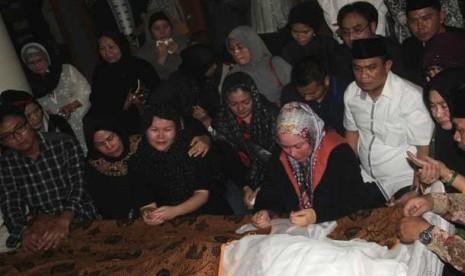 Gubernur Banten Atut Chosiyah (tengah) bersama keluarga besarnya berdoa di depan jenazah suaminya Hikmat Tomet, di Serang, Sabtu (9/11).