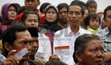 Gubernur DKI Jakarta, Joko Widodo berfoto bersama dengan warga usai membagikan Kartu Jakarta Sehat di kelurahan Marunda, Jakarta Utara, Senin (12/11).   (Adhi Wicaksono)
