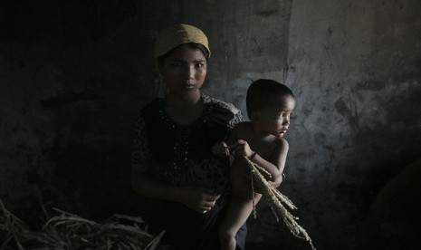 Hla Hla May, a Rohingya Muslim woman displaced by violence, holds her one year old daughter Roshan at a former rubber factory that now serves as their shelter, near Sittwe April 29, 2013.